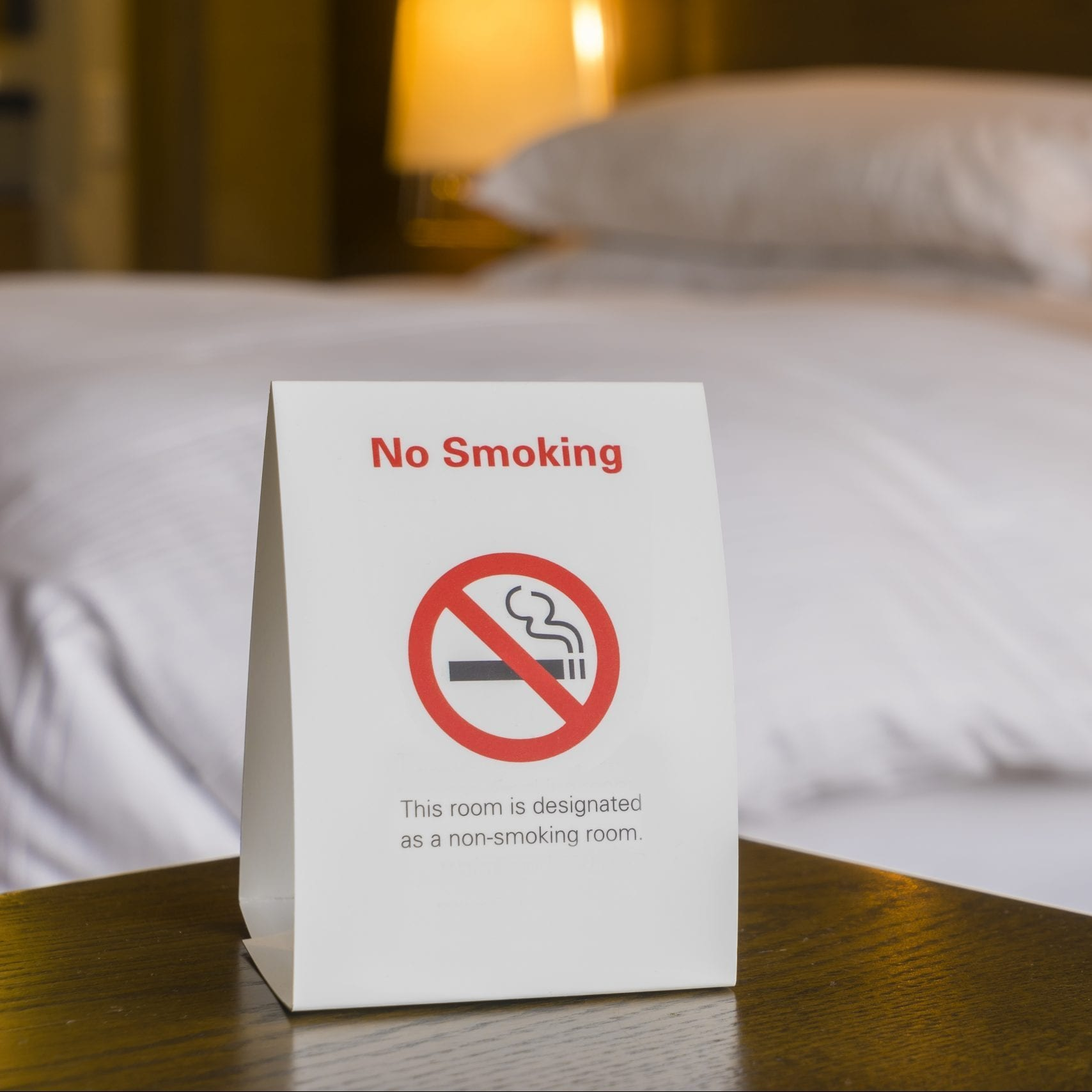 Non smoking hotel room with sign and bed as background